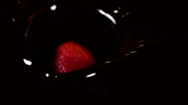 Two videos of strawberries falling into chocolate -real slow motion