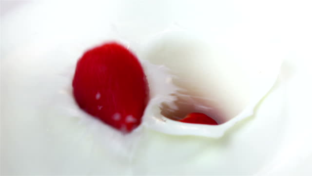 Two videos of strawberries falling into yogurt -real slow motion
