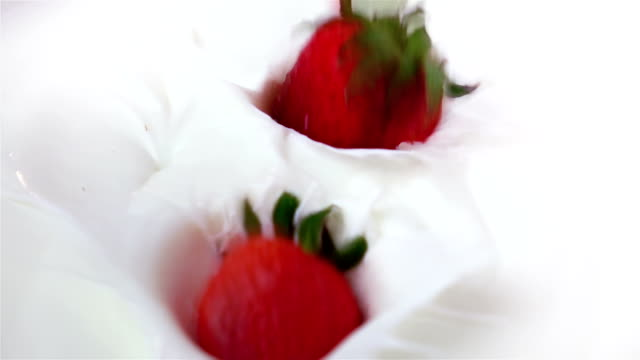 Two videos of strawberries falling into yogurt-real slow motion