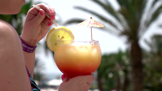 Two videos of woman drinking cocktail in real slow motion