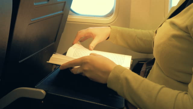Two videos of woman reading in the airplane in 4K