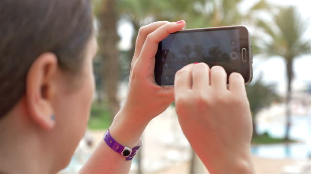 Two videos of woman taking a picture in 4K