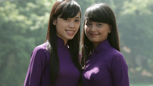 two vietnamese women wear ao dai as they smile and pose at the temple of literature. - ベトナム点の映像素材/bロール