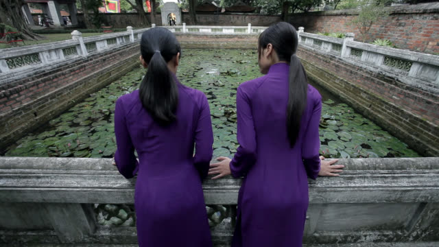 stockvideo's en b-roll-footage met two vietnamese women wear traditional ao dai as they lean against a railing at the well of heavenly clarity. - bukken