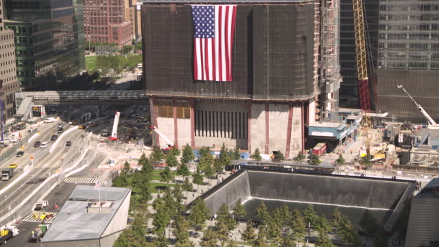 two views of a large national flag hanging from the construction site for the new world trade center above 'reflecting absence', the national september 11 memorial, manahattan, new york city, usa. - september 11 2001 attacks stock videos & royalty-free footage
