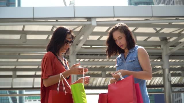 two walking women with shopping bags - dorso umano video stock e b–roll