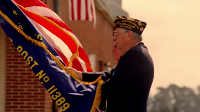 two war veterans carrying flags and leading parade in street while spectators applaud in background / california - veteran stock-videos und b-roll-filmmaterial