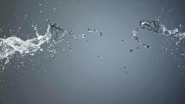SLO MO Two water jets colliding on grey background