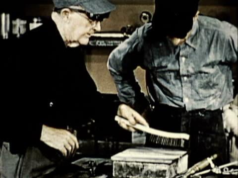 vídeos y material grabado en eventos de stock de 1965 ms two welders cleaning welded plate on workbench / usa / audio - accesorio de cabeza