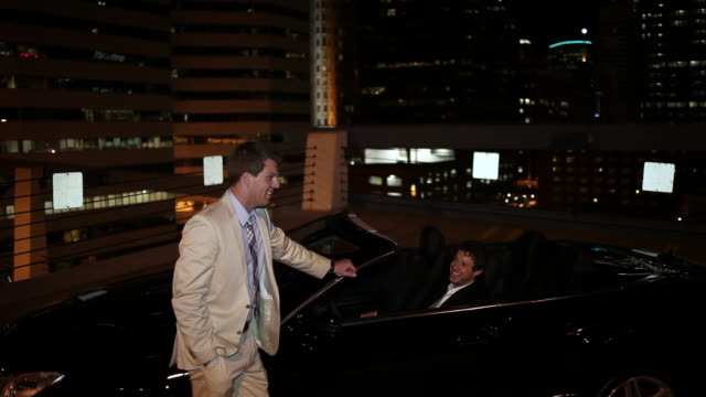 MS TD Two well dressed young man standing together on modern convertible car at night in urban area laughing and smiling / Minneapolis, Minnesota, United States