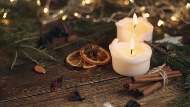 two white burning candles on the table between spruce branches and spices - christmas decore candle stock videos & royalty-free footage