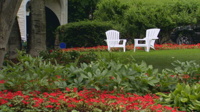 Two white chairs in a garden setting