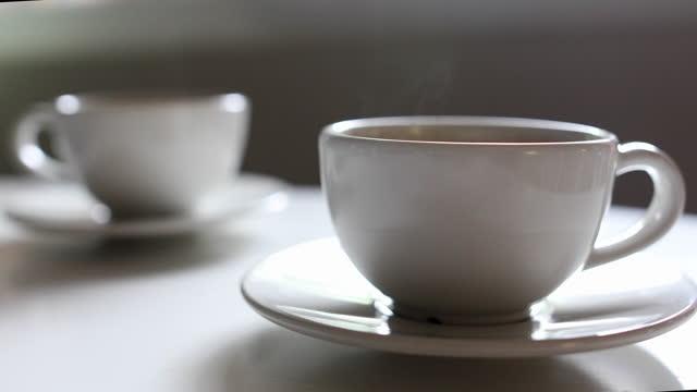 två vita kaffekoppar som placerar sig tillsammans på vitt bord - het dryck bildbanksvideor och videomaterial från bakom kulisserna