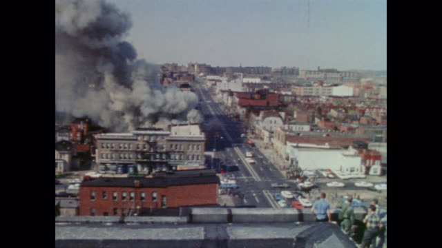 vídeos y material grabado en eventos de stock de two white men observe a burning building from the safety of the roof below an american flag at half mast as the camera zooms in on the burning... - 1968