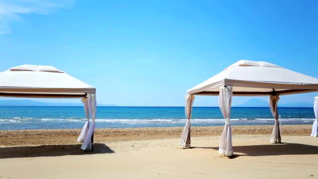 vídeos de stock, filmes e b-roll de duas tendas brancas na praia sob o claro céu azul - árvore tropical