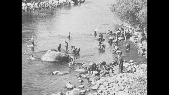 two wide overhead shots of men digging and panning for gold in river / men digging and panning for gold on bank of river / closer shot of men panning... - panning 個影片檔及 b 捲影像