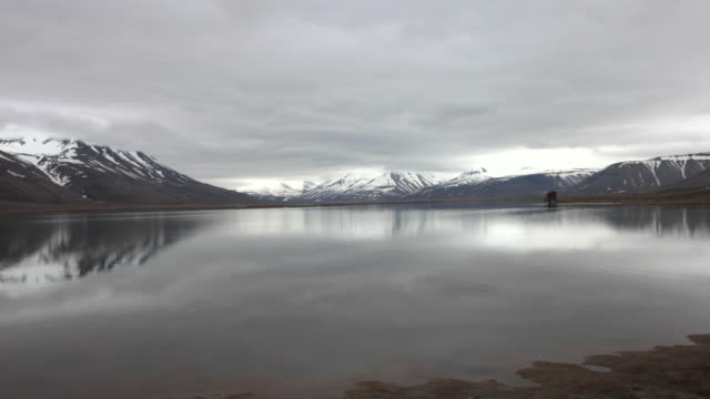 two wild geese flying over a magnificent lake with mountains covered by snow in the back, spitsbergen, svalbard; fantastic arctic scenery - 30 seconds or greater stock videos & royalty-free footage
