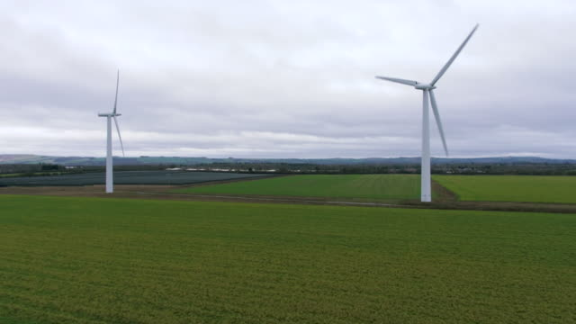 vidéos et rushes de two wind turbines spin against white clouds - route de campagne