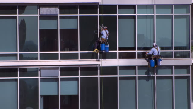 two window cleaners repelling from a hotel in downtown austin - curtain wall facade stock videos and b-roll footage
