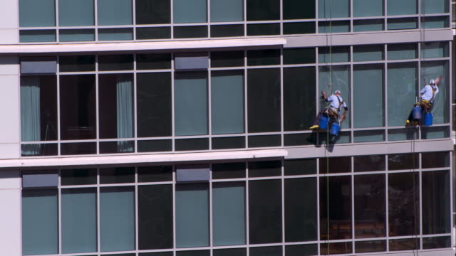 two window cleaners repelling from a hotel in downtown austin - cleaner stock videos and b-roll footage