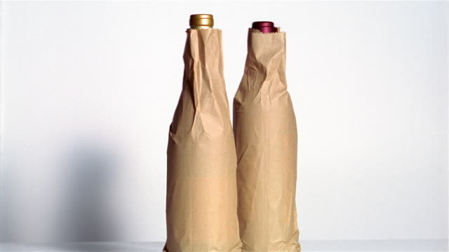 cu shaky two wine bottles wrapped on paper - eingewickelt stock-videos und b-roll-filmmaterial