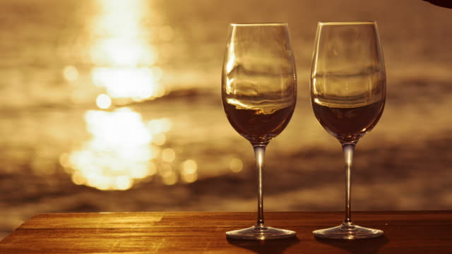 slo mo two wine glasses on the table by the sea at sunset - anticipation stock videos & royalty-free footage