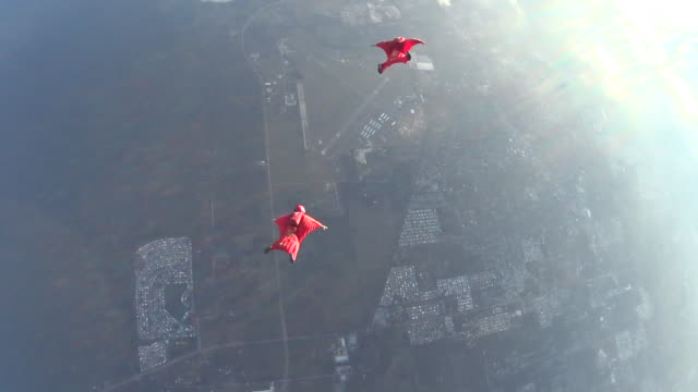 two wingsuit pilots in free fall performing acrobatics - arms outstretched stock videos and b-roll footage