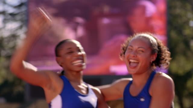 vídeos de stock e filmes b-roll de two woman athletes celebrate as a giant video screen shows their image. - campeonato desportivo