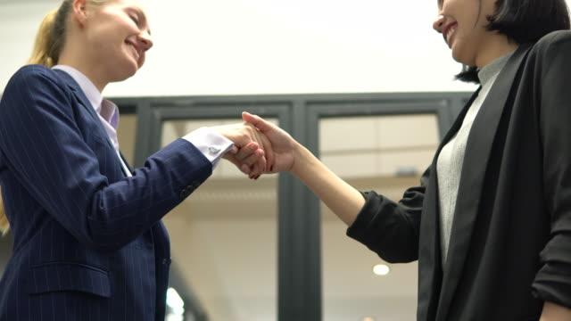 2人の女性ビジネスパートナー握手、収益性の高い契約、協力 - 大使点の映像素材/bロール
