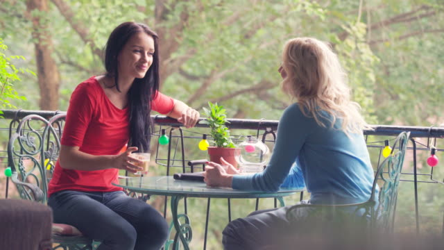 WS two woman chatting in a cafe