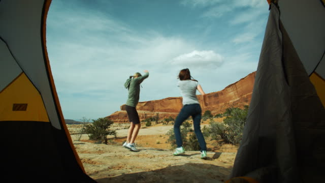 two woman dancing on a campout
