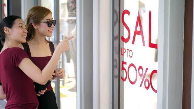 ショッピングストアで話し合う二人の女性 - ショーウィンドウ点の映像素材/bロール