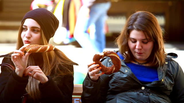 two woman eating bagels on the bench - bagel stock videos & royalty-free footage