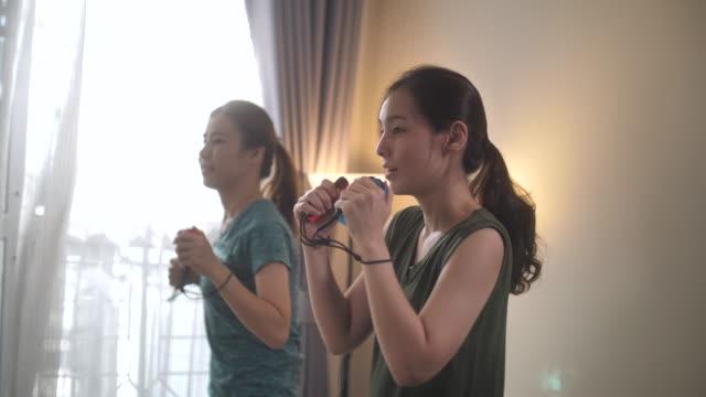 vidéos et rushes de deux amies de la femme de boxe faisant de l'exercice sur le jeu vidéo à la maison - rester à la maison expression