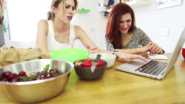 Two woman friends eat fruit and watch a laptop
