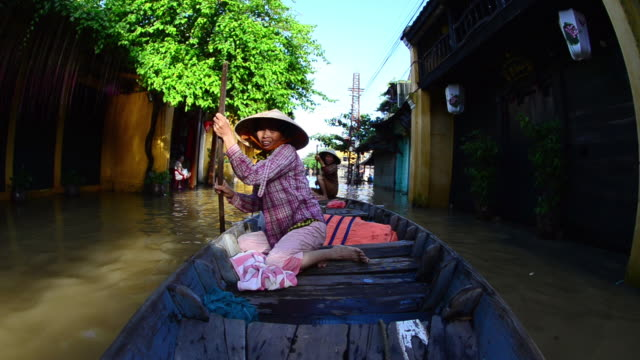 MS Two woman in conical hat rowing on flooded Hoi An streets / Hoi An, Quang Nam, Viet Nam