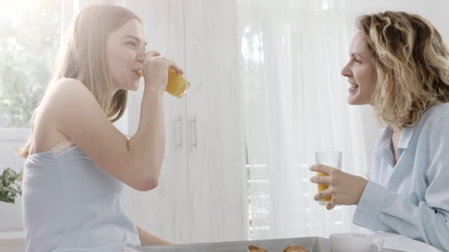two woman in the bed talking, drinking orange juice - orange juice stock videos & royalty-free footage