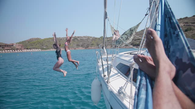 two woman jumping off a sailboat, swimming near islands in greece. - slow motion - segelschiff stock-videos und b-roll-filmmaterial