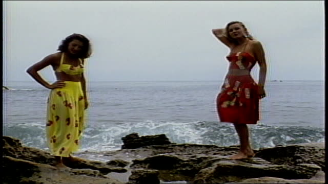 two woman modeling sun dresses while standing on rock by ocean - sommerkleid stock-videos und b-roll-filmmaterial