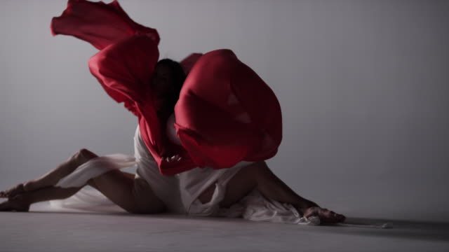 two woman sitting back to back draped with red silk fabric that moves in wind - rosso video stock e b–roll