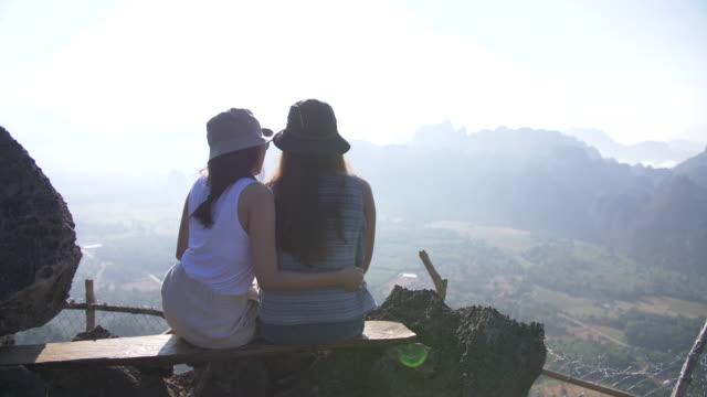 山の頂上に座って、スマートフォンで写真を撮るために selfie スティックを使用している2人の女性。リラクゼーションをお楽しみください。 - 自画像点の映像素材/bロール