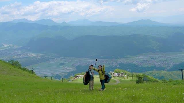 two woman taking selfie at mountain. - ハイキング点の映像素材/bロール