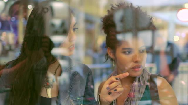 vídeos de stock, filmes e b-roll de medium handheld two woman talking and window-shopping indoors in mall - shopping center