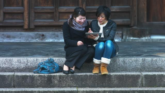 日本のお寺でデジタル タブレットを使用して 2 つの女性 - 談笑する点の映像素材/bロール