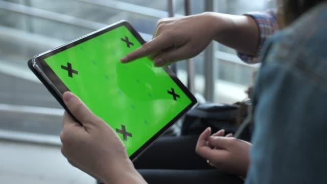 two woman using digital tablet green screen - digital tablet stock videos & royalty-free footage
