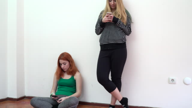 Two Woman Using Smart Phone Indoors