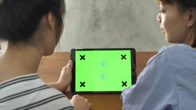 vídeos de stock, filmes e b-roll de duas mulher usando o tablet pc em modo paisagem em casa - modelo web