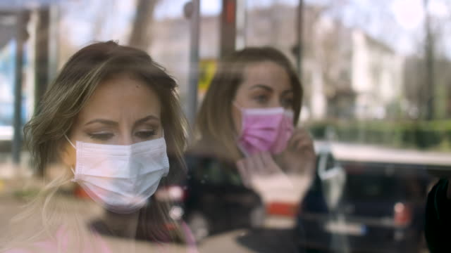 two woman wearing surgical mask sitting at public transportation - public transport stock videos & royalty-free footage