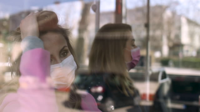 vídeos de stock e filmes b-roll de two woman wearing surgical mask sitting at public transportation - amizade feminina
