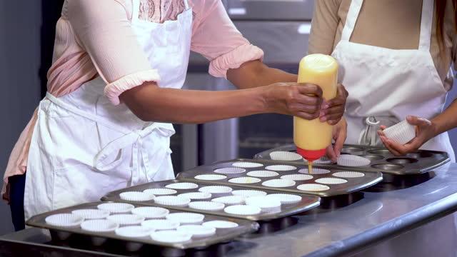 zwei frauen, die in der bäckerei arbeiten und cupcakes herstellen - multi ethnic group stock-videos und b-roll-filmmaterial